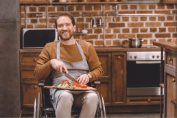 Dinner preparation. Serious brunette man in wheelchair using knife while preparing a fresh salad