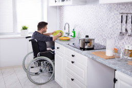 man in wheelchair washing dishes at an accessible sink in his kitchen